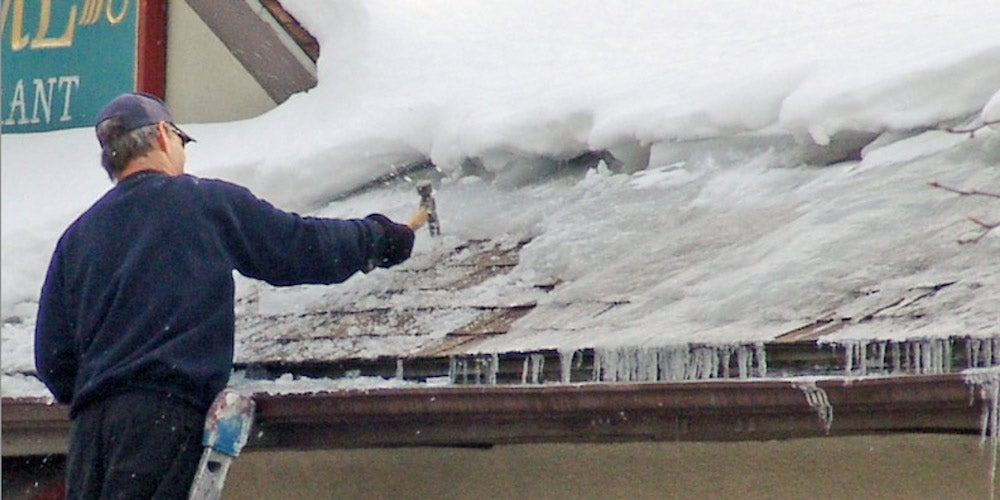 A homeowner using a hammer to break up an ice dam on their roof