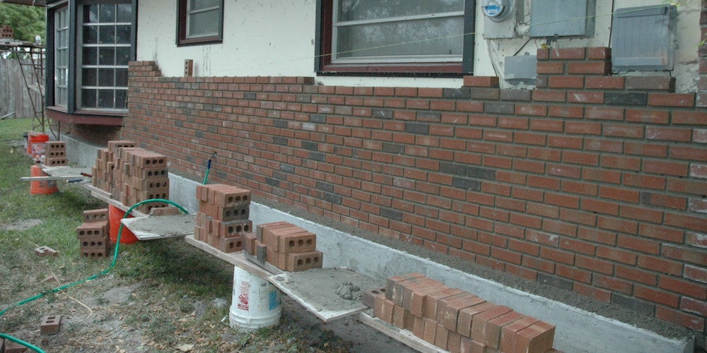 Authentic brick siding being applied to a home