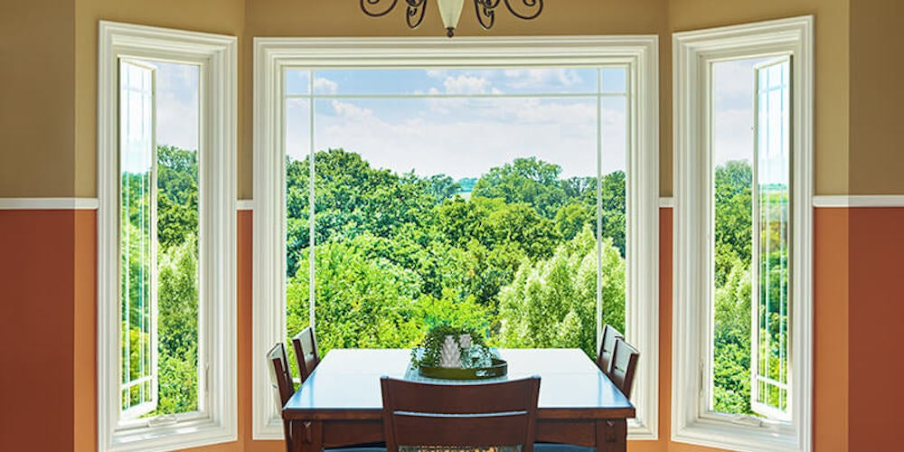 Dining table in front of a bay window