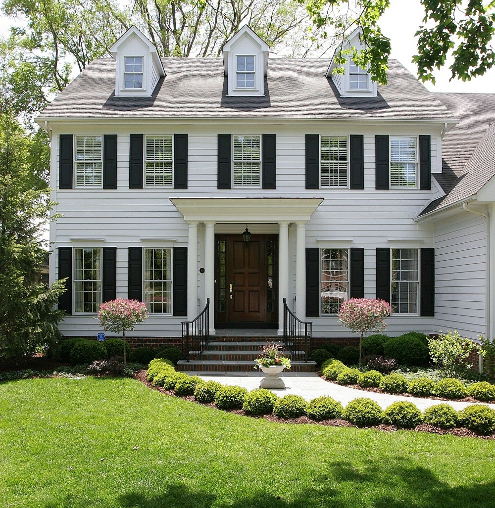 A white colonial home with black shutters and grey shingles
