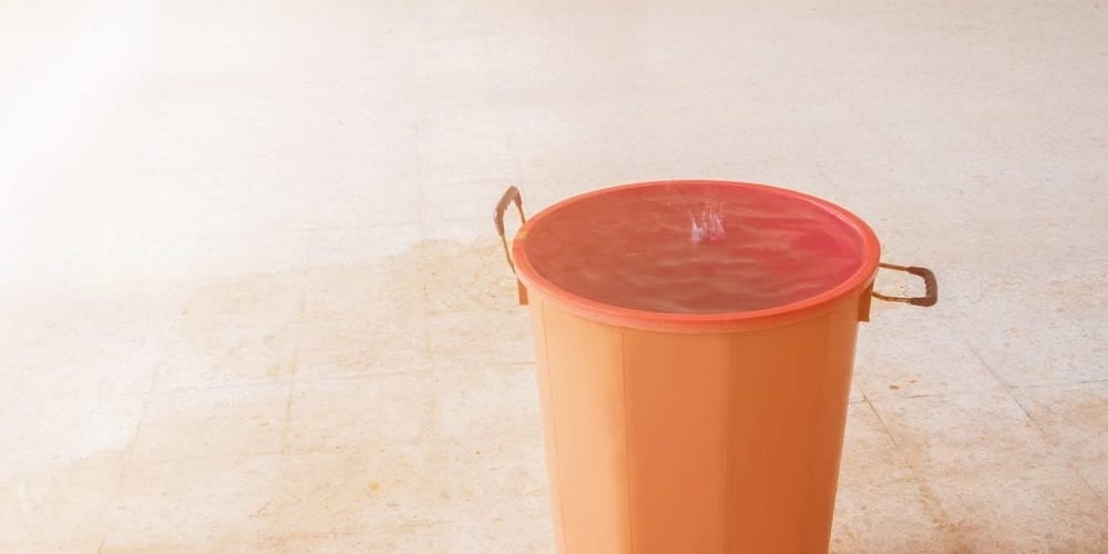 An orange bucket collecting a roof leak