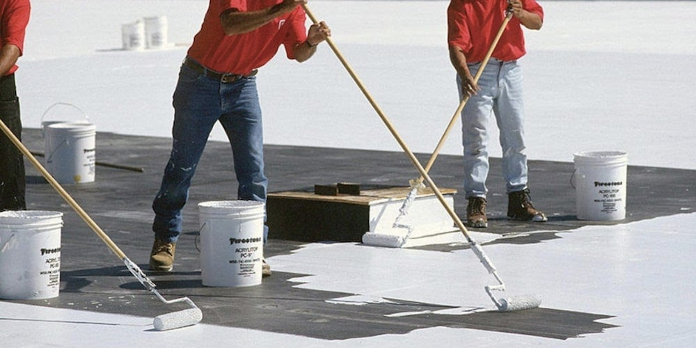 Professional installing cool roof coating on a flat roof