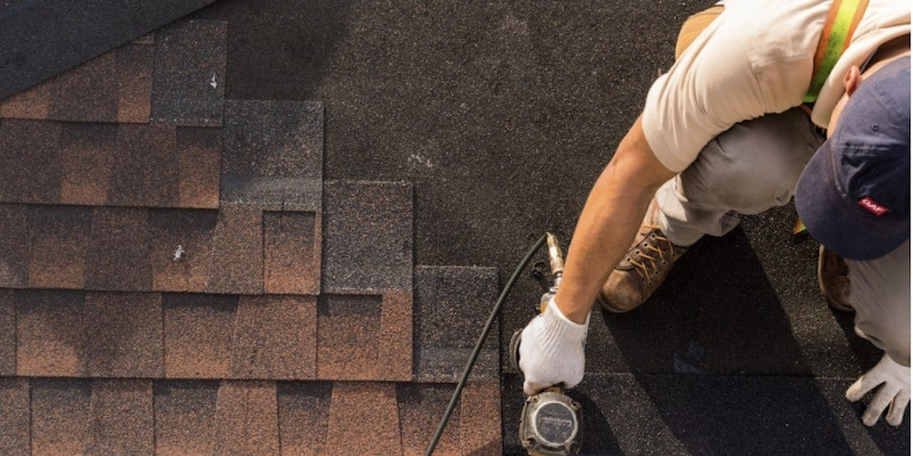 Professional roofing contractor installing GAF shingles on a roof