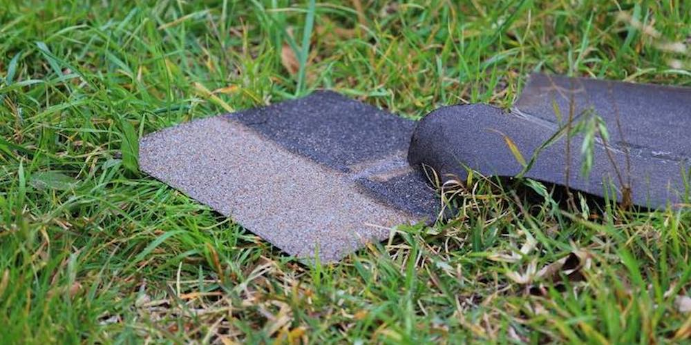 Damaged GAF shingles blown off a roof laying in grass