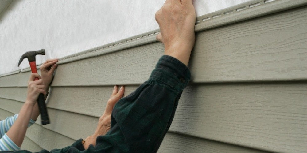 DIY repairs being done to siding on a residential home