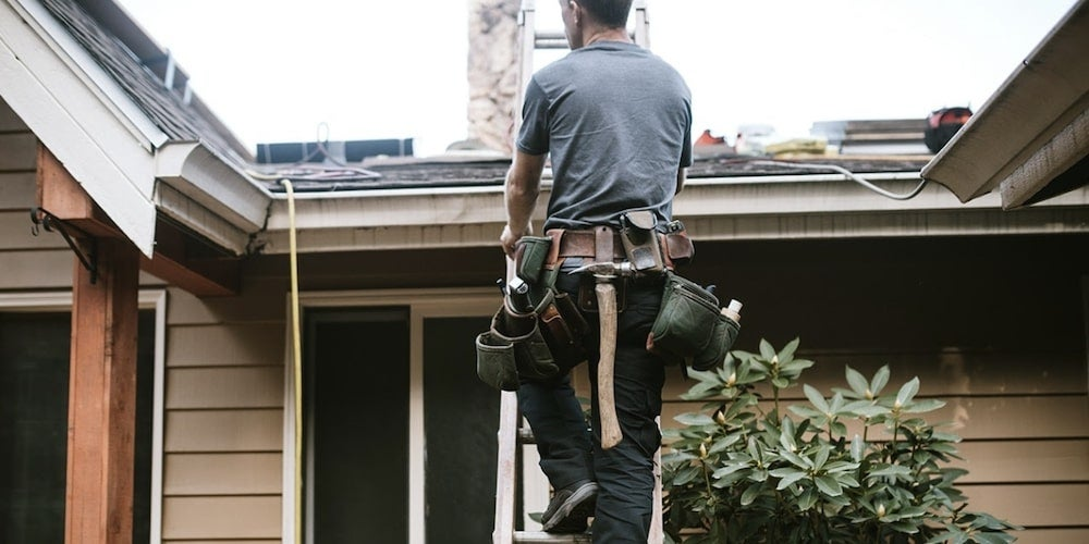 Professional roofing contractor standing on a ladder in front of a residential roof