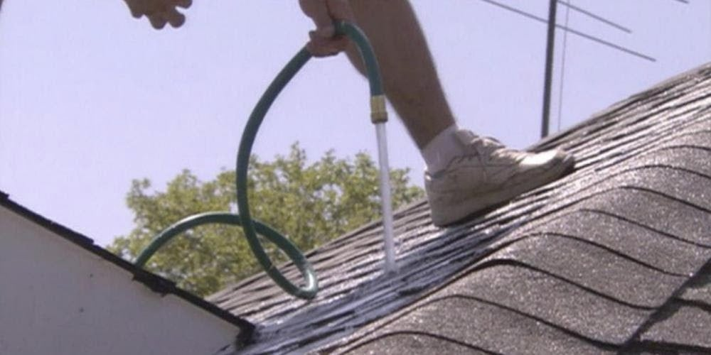 A homeowner spraying a roof with a garden hose to detect a leak