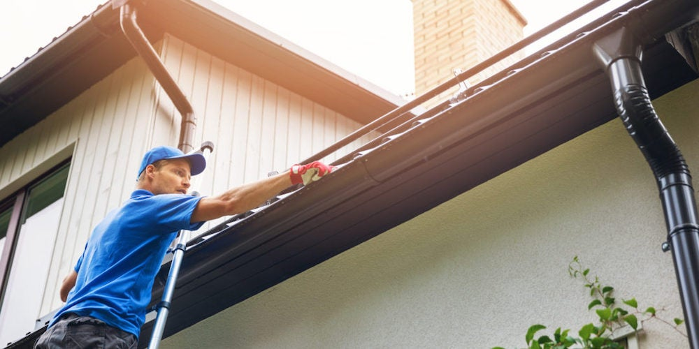 A professional performing gutter maintenance on a home