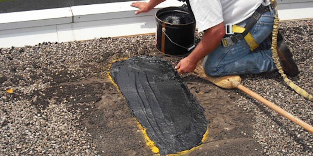 A contractor repairing a flat roof