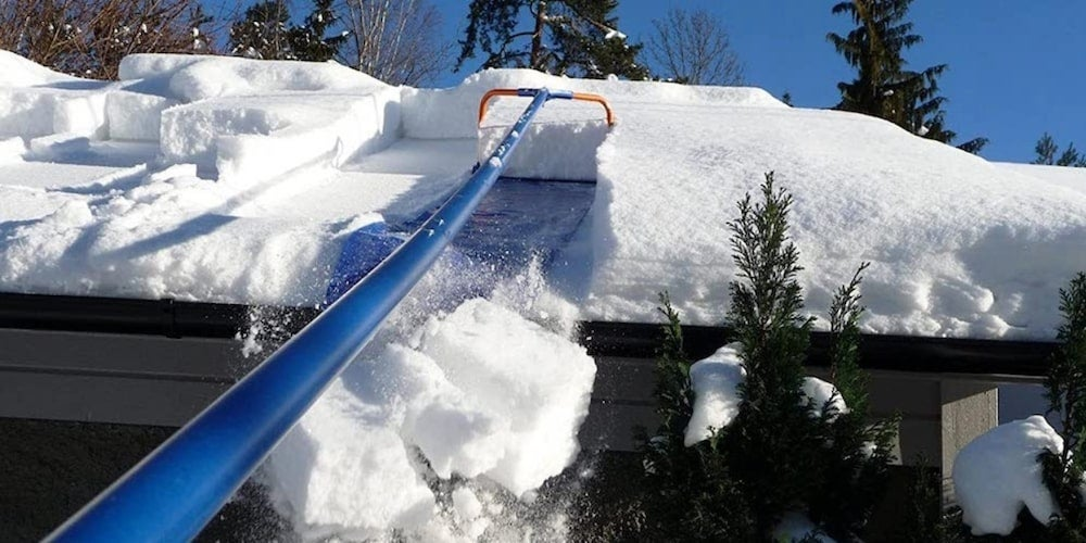 A homeowner using a roof rake to remove snow from a roof