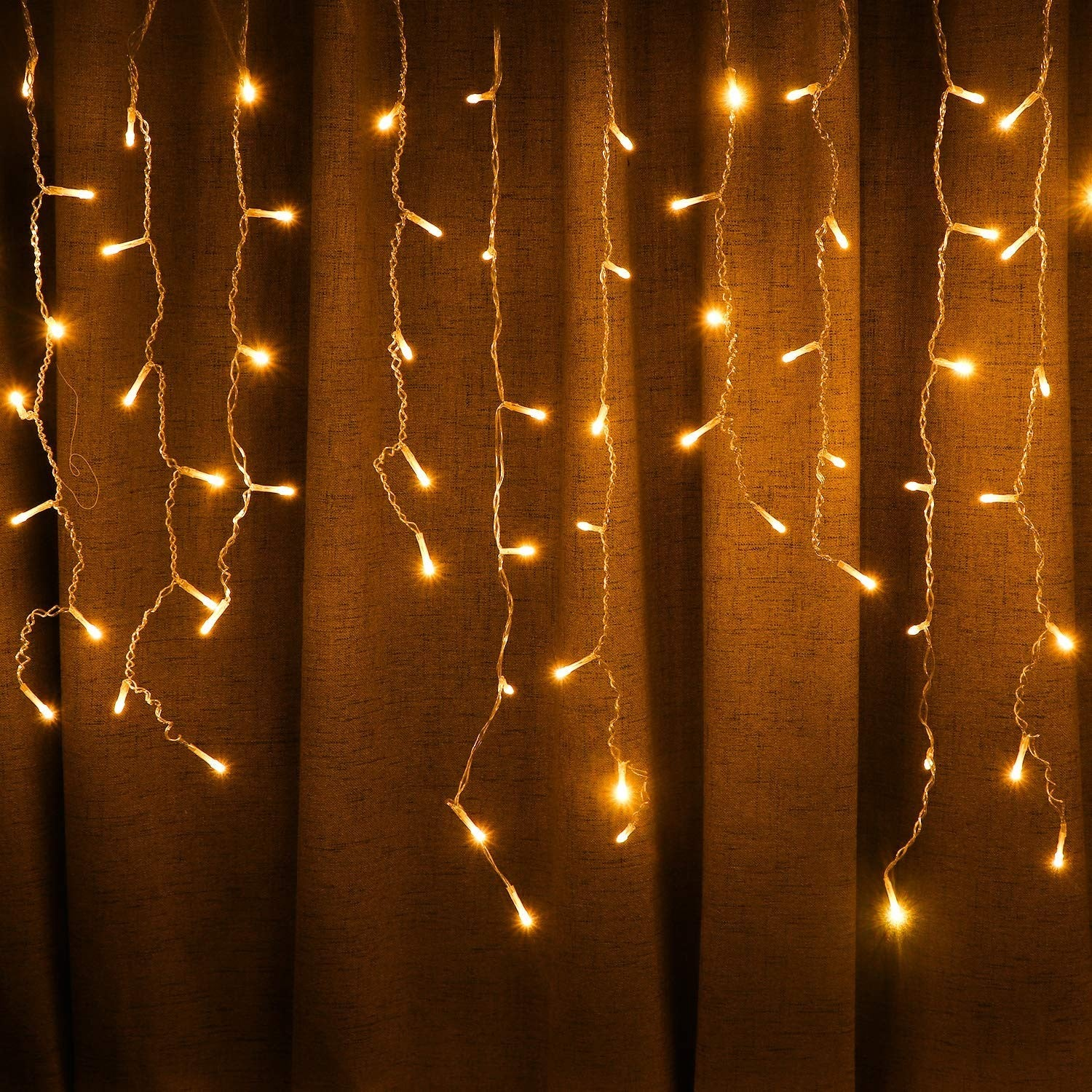 Solar-powered icicle lights hanging in front of a curtain