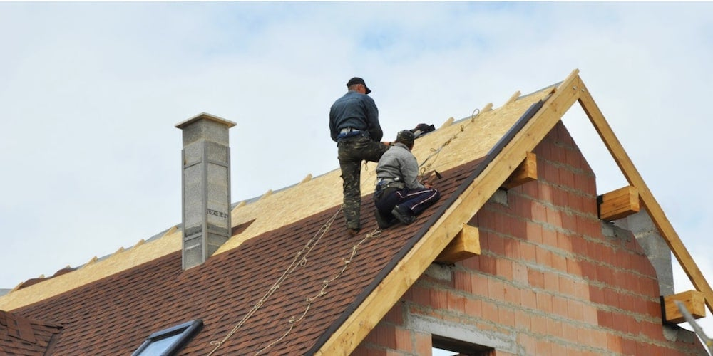 Professional roofers installing IKO shingles on a roof