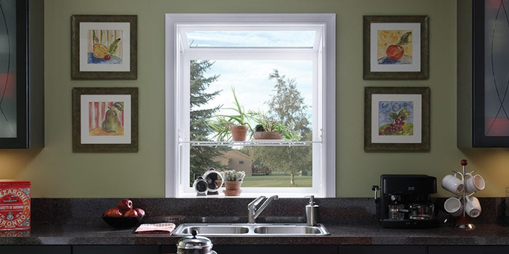 Kitchen garden window above a sink with a few plants