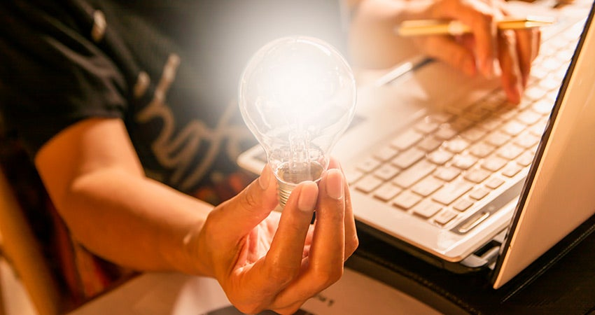 Guy holding light bulb sitting at computer