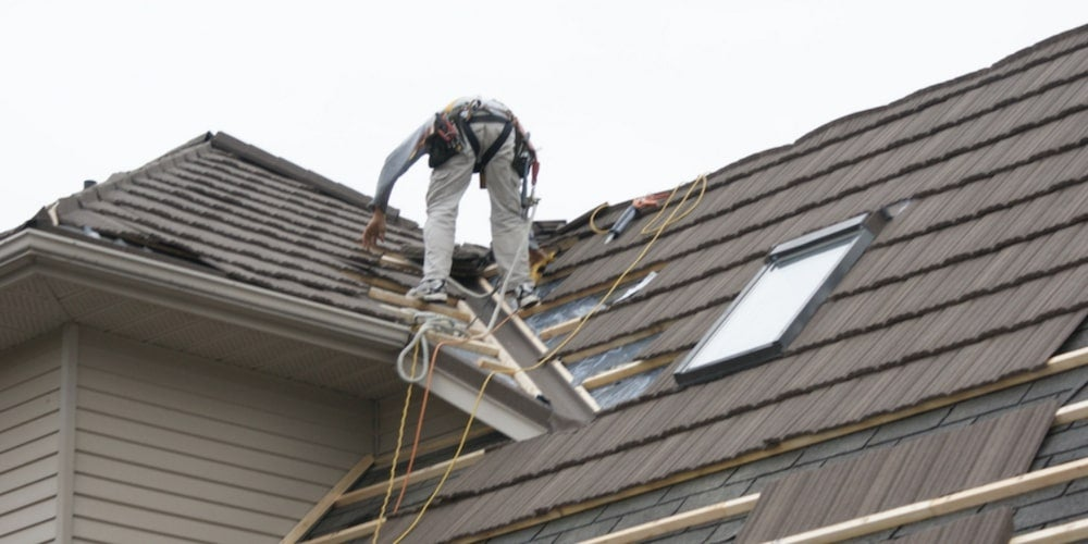 A roofer installing a stone-coated steel roof on a residential home