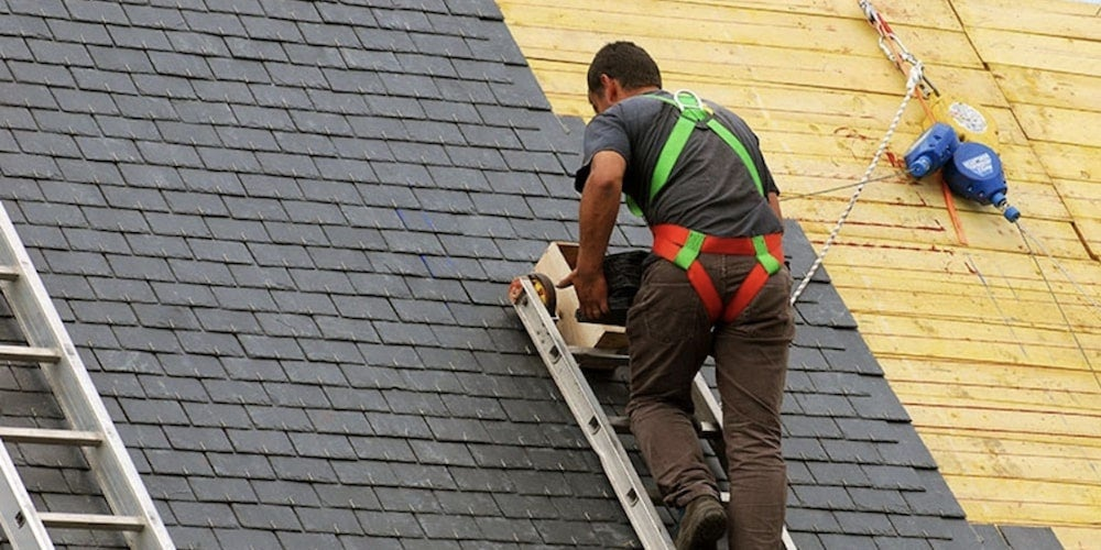 Asphalt shingle roof being worked on by a professional roofer