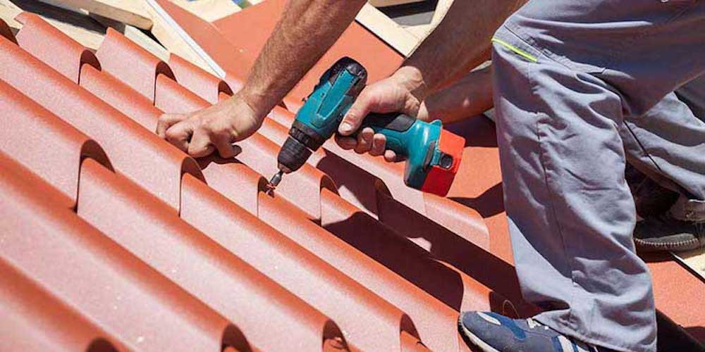 Metal roof shingles being drilled into a roof by a roofing professional