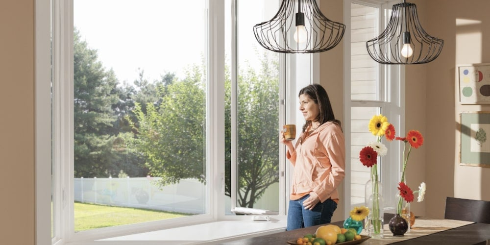 Milgard bay window in a kitchen with a person looking out onto the lawn