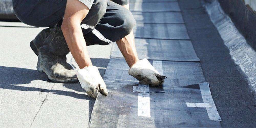 A homneowner attempting DIY flat roof repair