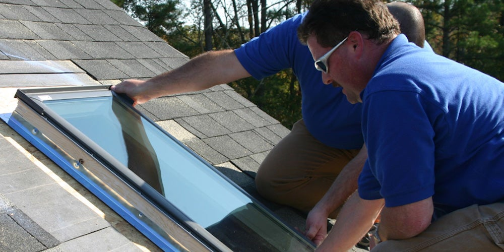 Two homeowners placing a glass fixed skylight on their roof