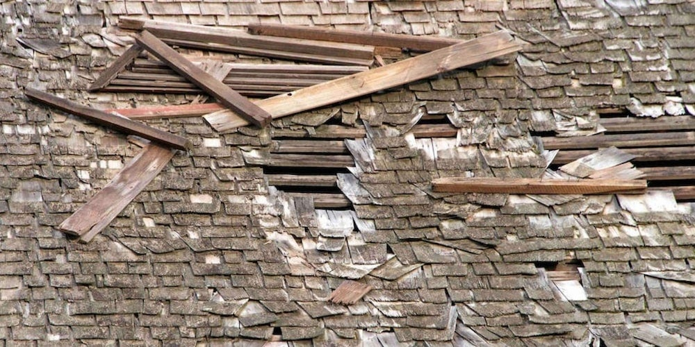 A residential roof with missing shingles and exposed beams
