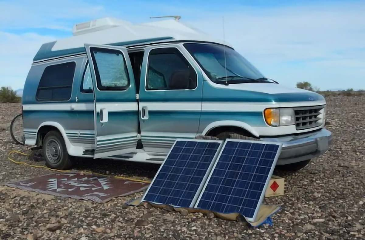 Two small solar panels placed in front of a camper van parked outdoors