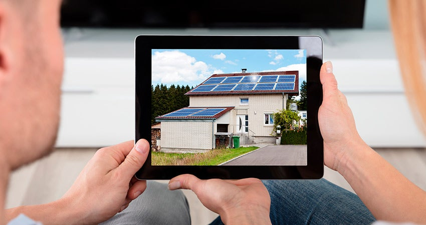 Couple holding tablet showing home with solar