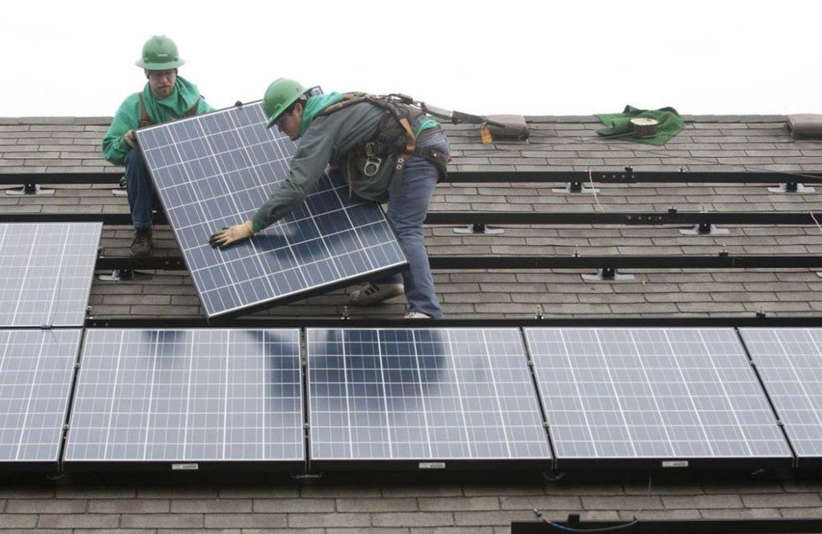 two installers on a roof with solar panels