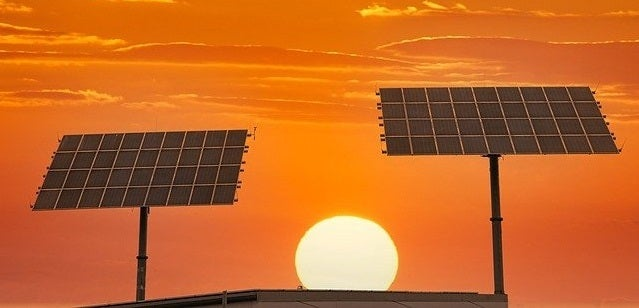 The sun sets behind two panel-mounted solar panel arrays