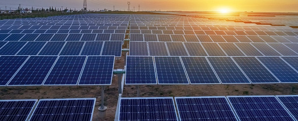 rows of ground mounted solar panels with a rising sun in the background