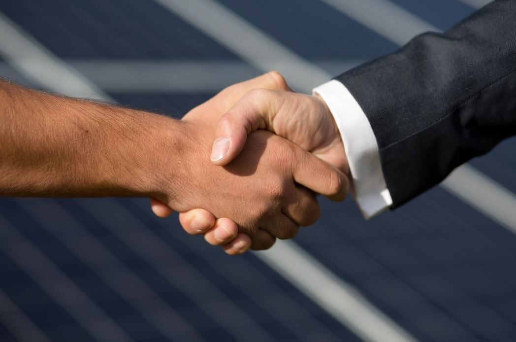 two men's forearms and hands showing, handshake signaling a business deal