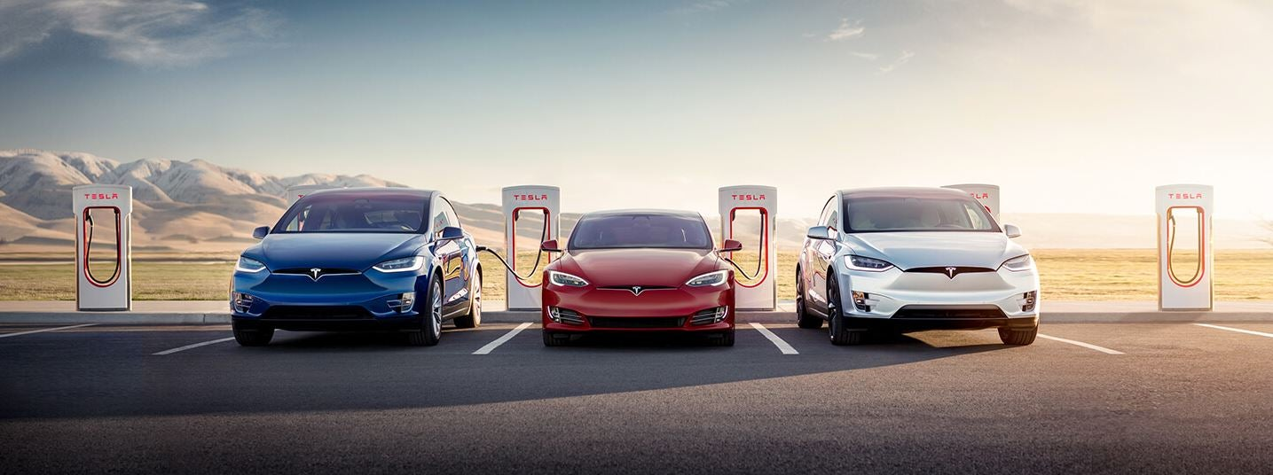 Tesla cars lined up in front of superchargers against a mountainous background with a setting sun