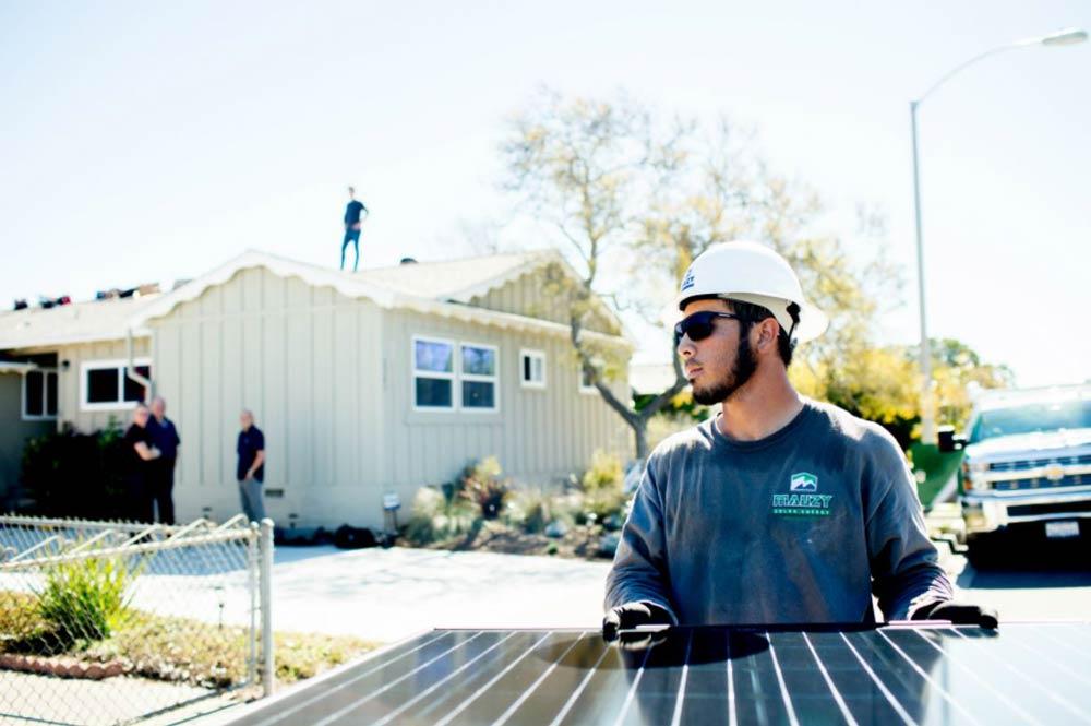 a solar installer carrying a solar panel towards a home
