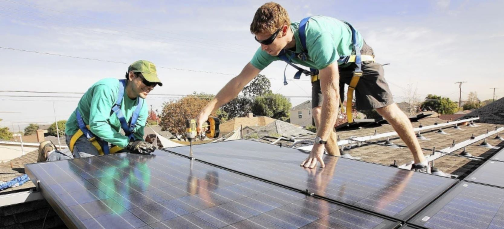 two men standing on top of solar panels
