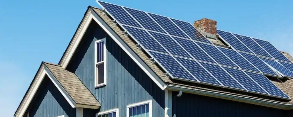 A blue home with solar panels on the roof