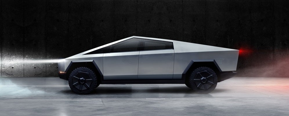 A silver Tesla Cybertruck against a black wall