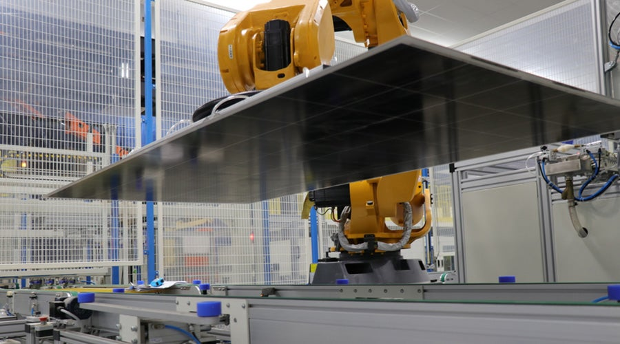 A robotic arm lifts a black solar panel on a factory assembly line.