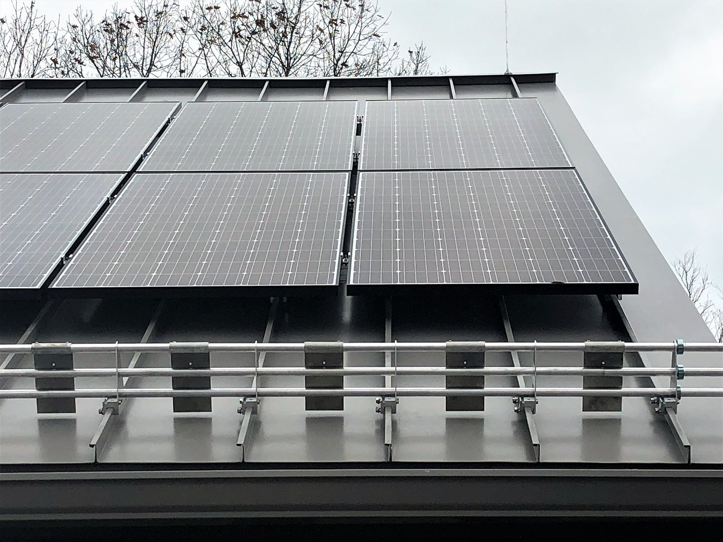 A solar panel snow guard holding back a few feet of snow on a roof