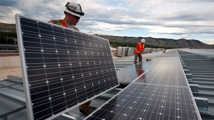 solar installers placing solar panels on racking, mountains in the background
