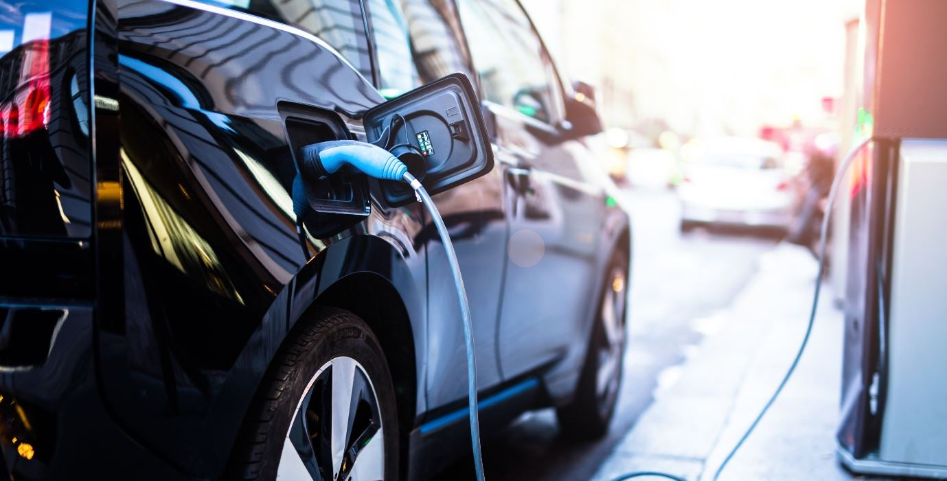 A black electric car being charged