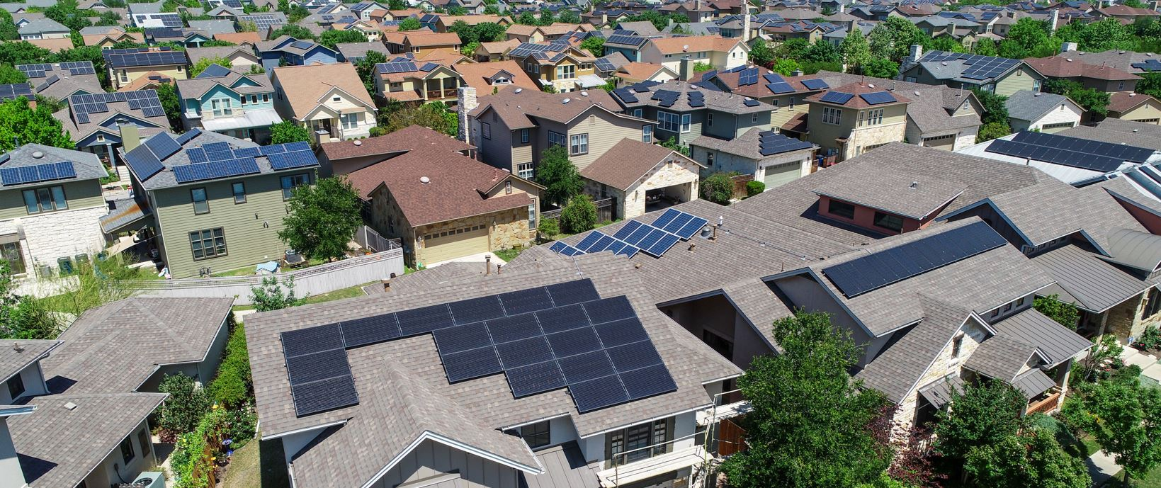 a suburban area featuring homes with solar panels on their roofs
