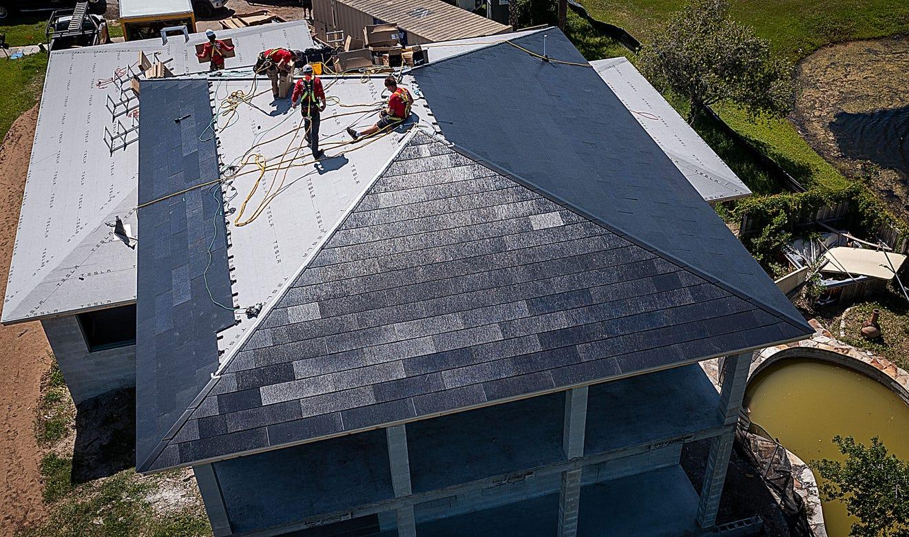 solar installers installing a tesla solar roof