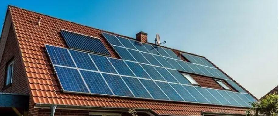 Grape Solar brand solar panel array on a terracotta-shingled roof home