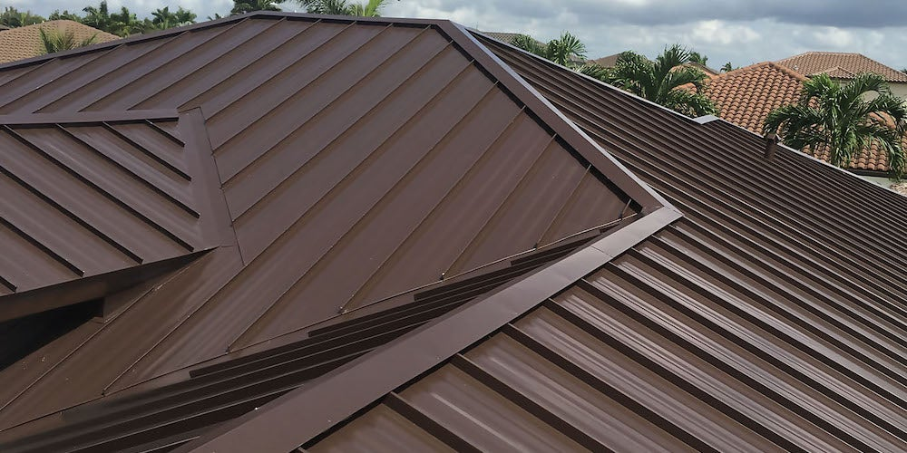 Galvalume steel roof installed on a residential home with palm trees in the background
