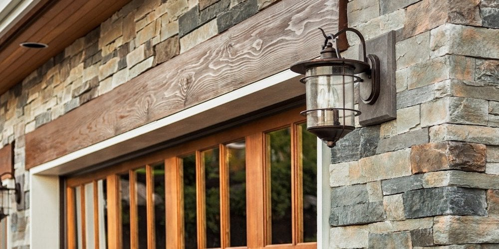 Stone veneer siding on a residential home installed above windows