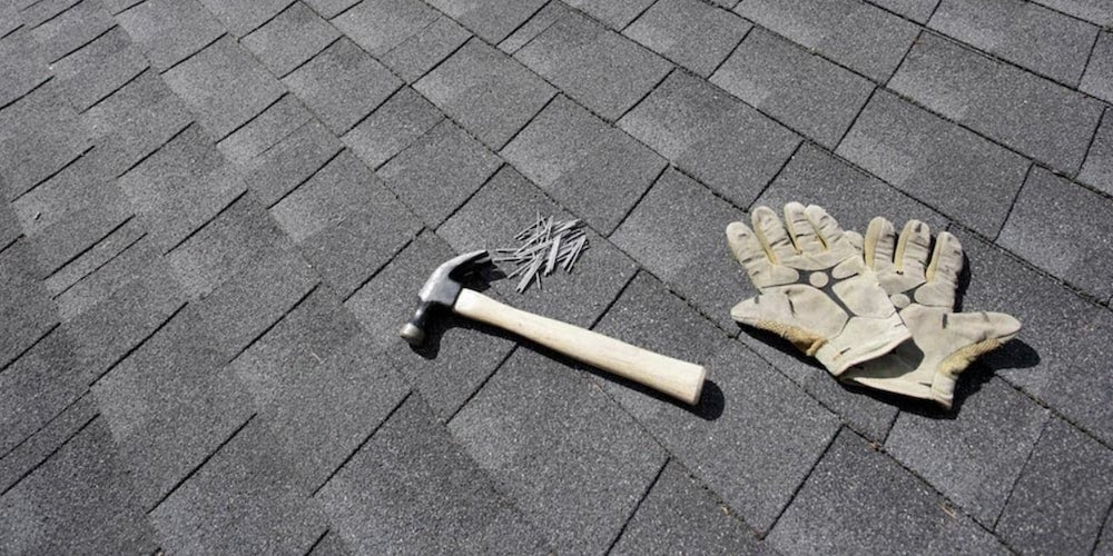 A hammer, nails, and gloves resting on a residential roof