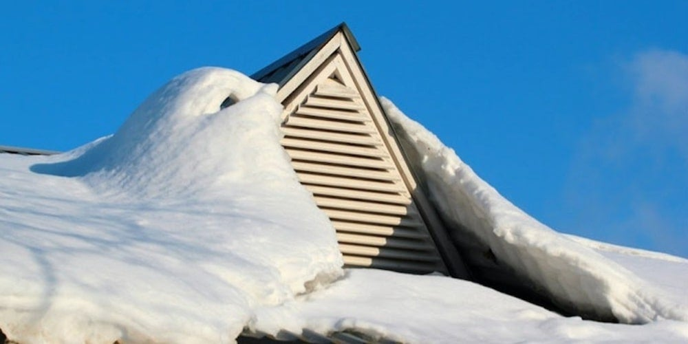 A roof vent on a residential roof covered in snow