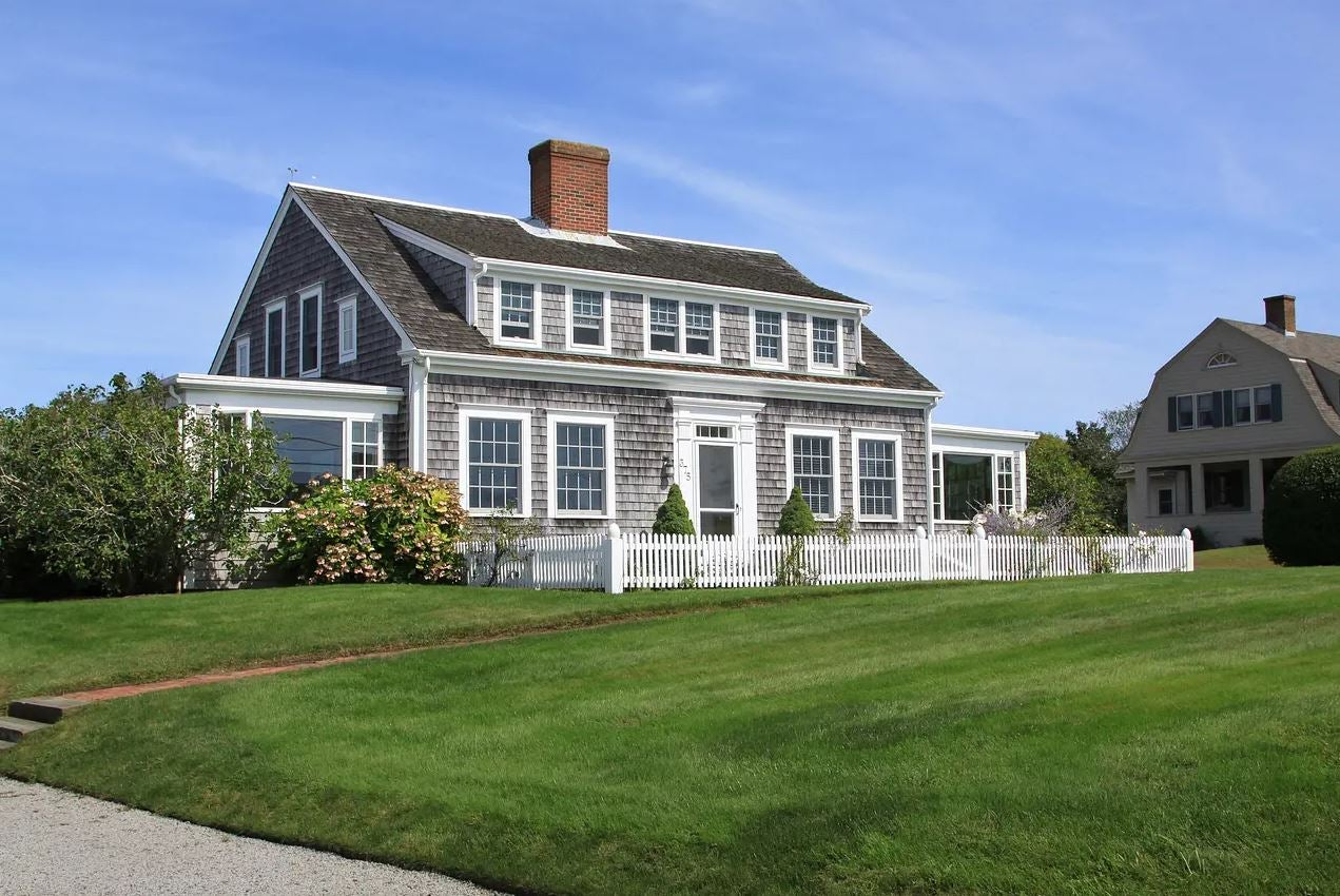 A Cape Cod style home with a large front lawn, wooden siding and a grey roof