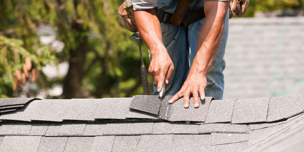 A professional roofer cutting shingles on a roof