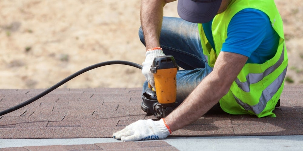 A professional contractor installing shingles on a roof